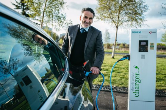 Tesla driver Ron Mackenna powers up his Tesla at a charging point in Glasgow