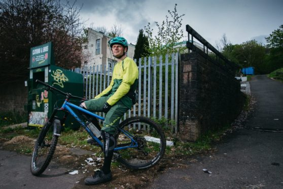 Mountain biker Ruairidh MacKenzie out side St Martin's Church in Castlemilk, Glasgow, which was meant to be turned into a mountain bike hub, as a legacy project after the Commonwealth Games in Glasgow.