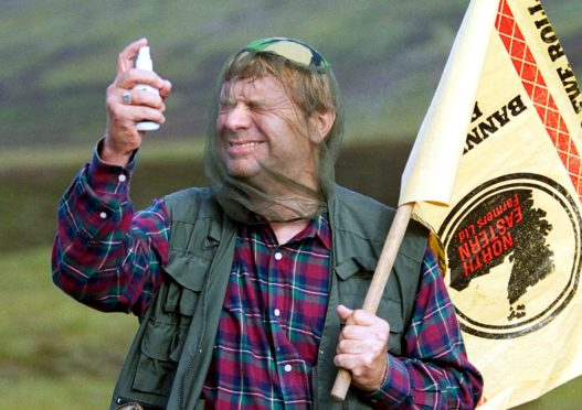 A man wearing a net sprays midge repellent in the Highlands