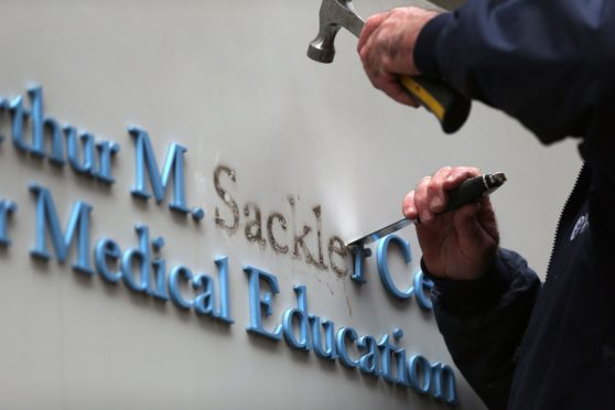 Signage featuring the Sackler family name is removed from a building in Boston