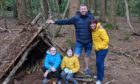 Claire Spreadbury and her family, outside the den they built in the forest