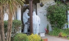 Funeral directors in hazmat suits enter Home Farm care home on Skye, where 10 residents died of Covid in May last year