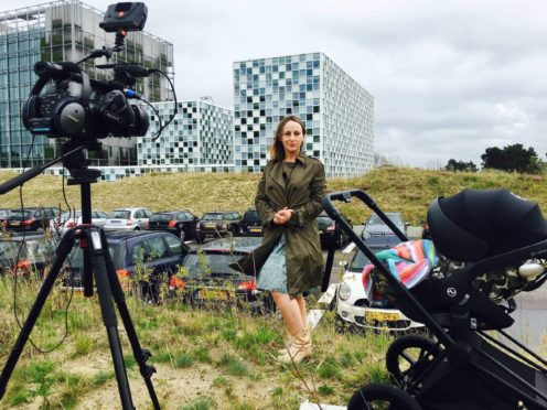 BBC foreign correspondent Anna Holligan reports live to camera from the International Criminal Court in The Hague with daughter Zena in baby buggy just out of shot