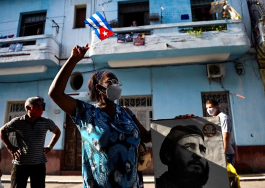An elderly woman in Havana waves a Cuban flag holding a poster of Cuban late leader Fidel Castro on July 26 – the day the Cuban government marked what was regarded as the start of the Cuban Revolution