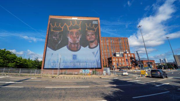 A digital mural of England players Marcus Rashford, Jadon Sancho and Bukayo Saka in Manchester