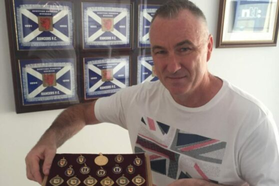 Ian Ferguson proudly displays his impressive medal haul from his time in Light Blue