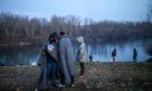 Migrants in Turkey prepare to cross the Evros River in March 2020