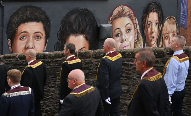 Apprentice Boys of Derry take part in the annual Relief of Derry march last Saturday, passing a mural depicting the TV show, Derry Girls