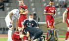 Andrew Considine is tended to by Aberdeen's medical team after going down injured in Baku