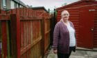 Helen Dillet next to the disputed fence in the garden of her lifelong home in Fauldhouse