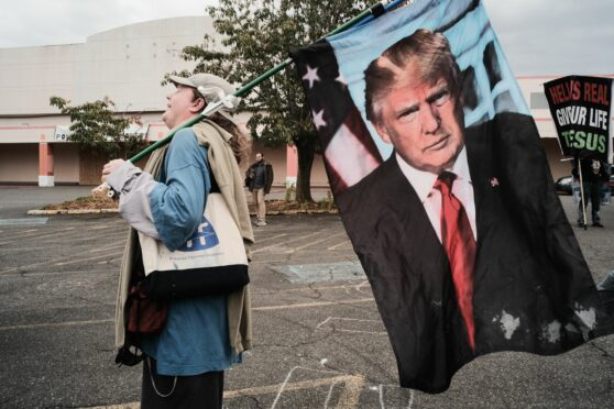 A supporter carries a Donald Trump flag during a rally held by far-right Proud Boys in Portland, Oregon last weekend