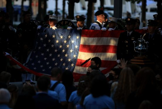 Members of the New York police and fire departments hold a flag for the national anthem at the 9/11 Memorial is seen on the 20th anniversary of the September 11 attacks in Manhattan, New York City.