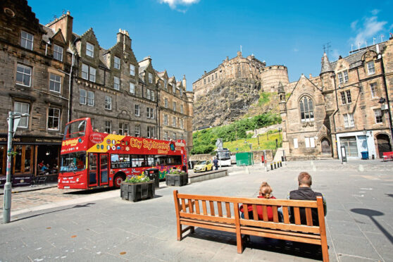edinburgh A City Sightseeing Bus in the Grassmarket with Edinburgh Castle visible beyond, in the city centre of Edinburgh.