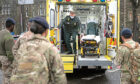 Members of the military practice loading and unloading a stretcher into an ambulance at Maindy Barracks.