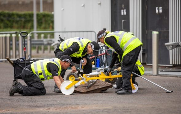 Police lift manhole covers during checks at Glasgow's SEC last week ahead of Cop26