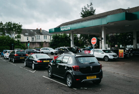 Cars queue at Morrisons petrol station on the south side of Glasgow yesterday as drivers panic-buy