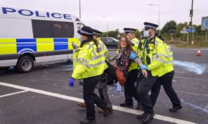 Police officers carry away a protester