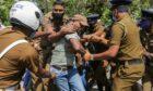 Sri Lankan police officers detain a protester in Colombo, Sri Lanka in June 2020