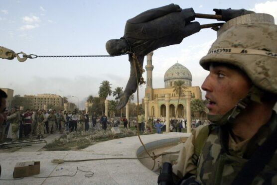 A US soldier looks on as the statue of Saddam Hussein is toppled in Firdaus Square, Baghdad on April 9, 2003