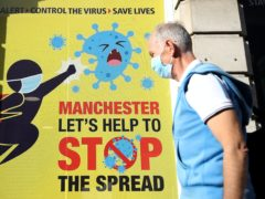 A person wearing a face mask walks past a Covid-19 sign on Deansgate (Martin Rickett/PA)