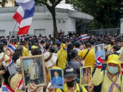 Supporters of the Thai monarchy display images of King Maha Vajiralongkorn, Queen Suthida and the late King Bhumibol Adulyadej (Gemunu Amarasinghe/AP)