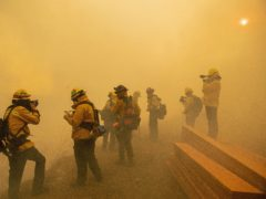 Firefighters are enveloped in smoke as they battle a blaze in Yorba Linda, California on Monday (Leonard Ortiz/The Orange County Register/AP)