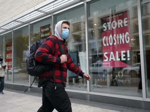 A passer-by walks past a store closing sign as the US economy faces fresh problems (Steven Senne/AP)