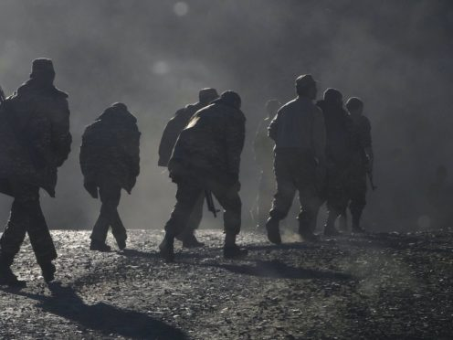 """Ethnic Armenian soldiers walk along the road near the border between Nagorno-Karabakh and Armenia, Sunday, Nov. 8, 2020. Azerbaijan's president says forces have taken control of the strategically key city of Shushi in Nagorno-Karabakh, but a Armenian Defense Ministry spokesman said on Facebook that """"fighting in Shushi is continuing."""" (AP Photo)"""