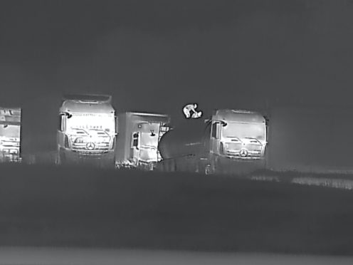 An individual, believed to be smuggler, loading a migrant in a lorry at night at a highway service area (Ocriest)