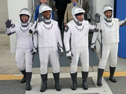 Nasa astronauts, from left, Shannon Walker, Victor Glover, and Michael Hopkins, and Japan Aerospace Exploration Agency astronaut Soichi Noguchi leave the Operations and Checkout Building on their way to launch pad 39A (John Raoux/AP)