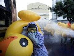 Pro-democracy protesters take cover with inflatable ducks as police fire a water cannon (Wason Wanichakorn/AP)