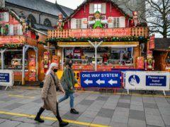 """People pass Christmas market stalls in Cardiff, where restrictions across Wales have been relaxed following a two-week """"firebreak"""" lockdown."""
