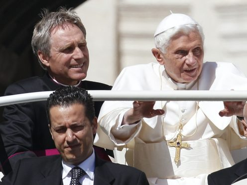 Pope Benedict XVI, right, arrives in St Peter's square at the Vatican for a general audience as his then-butler Paolo Gabriele, bottom, and his personal secretary Georg Gaenswein sitting in the car with him (Alessandra Tarantino/AP)