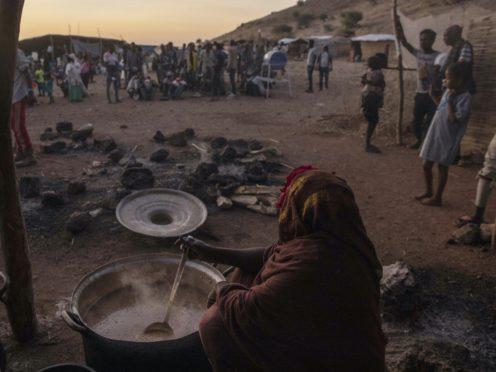 Sudanese women volunteer to cook for Tigray people who fled the conflict in Ethiopia's Tigray region, at Umm Rakouba refugee camp in Qadarif, eastern Sudan (Nariman El-Mofty/AP)