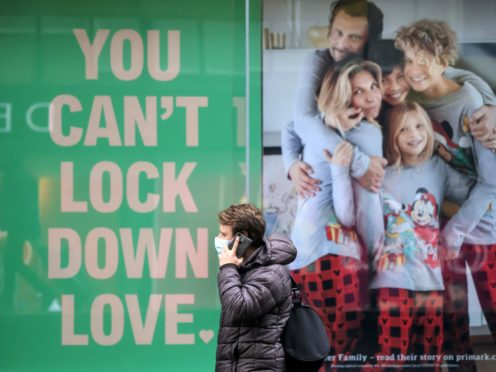 A man walks past a poster in the window of a Primark shop in Manchester (Danny Lawson/PA)