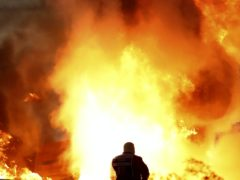 Staff extinguish flames from Romain Grosjean's car (Brynn Lennon/AP)