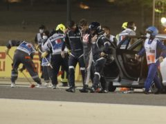 Haas driver Romain Grosjean of France is helped by medical staff after his horror crash in Bahrain (Hamad Mohammed/AP)