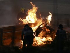 Haas driver Romain Grosjean's car burning after he crashed (Brynn Lennon/AP)
