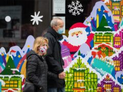 People wearing face masks pass a Christmas window display on Oxford Street, London (Dominic Lipinski/PA)