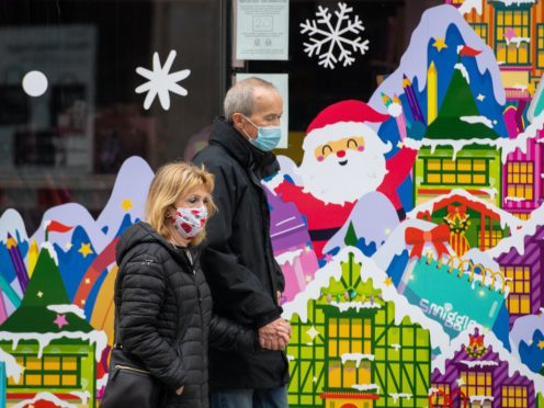 People wearing face masks pass a Christmas window display on Oxford Street, London (Dominic Lipinski/PA)