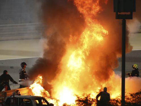 Staff extinguish flames from Romain Grosjean's Haas (Brynn Lennon/AP)