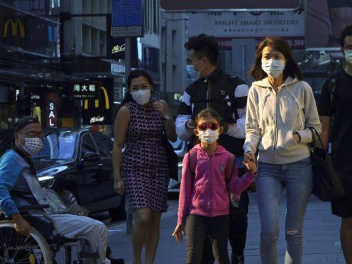 People wearing face masks to protect against coronavirus walk along a street in Hong Kong (KIn Cheung/AP)
