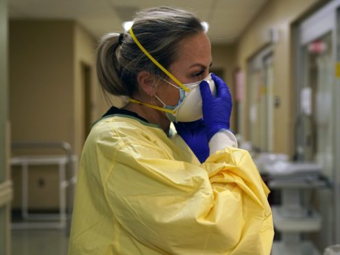 Registered nurse Chrissie Burkhiser puts on PPE as she prepares to treat a Covid-19 patient in a hospital in Memphis, Missouri. US hospitals are taking more desperate measures to lure staff as the coronavirus surges across the country (Jeff Roberson/AP)