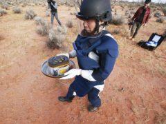 A Japan Aerospace Exploration Agency member retrieves the capsule dropped by Hayabusa2 in Woomera, southern Australia, on Sunday (JAXA via AP)