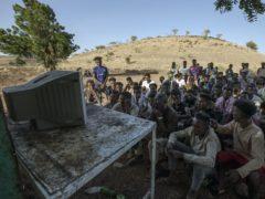 Tigranyan men who fled the conflict in Ethiopia's Tigray region, watch the news on a television, at Umm Rakouba refugee camp in Qadarif, eastern Sudan, Saturday, Dec. 5, 2020. (AP Photo/Nariman El-Mofty)