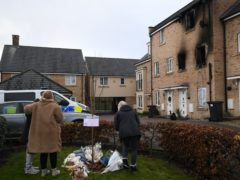 People lay flowers at the scene of a house fire on Buttercup Avenue, Eynesbury, Cambridgeshire (Joe Giddens/ PA)