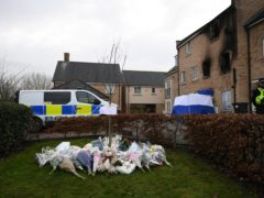 Floral tributes have been left at the scene of the blaze in Eynesbury, Cambridgeshire (Joe Giddens/PA)