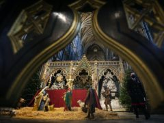 An abbey marshal walks past the Nativity crib and Christmas trees inside Westminster Abbey, London (Victoria Jones/PA)