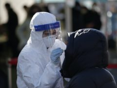 A medical worker wearing protective gear takes a sample from a woman during a Covid-19 testing in Seoul, South Korea (Lee Jin-man/AP)