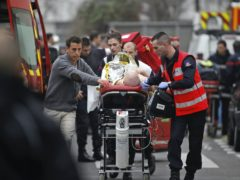 An injured person is taken to an ambulance after the shooting at Charlie Hebdo (Thibault Camus/AP)